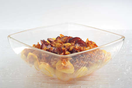 heatproof: Fried the onions pieces, the potatoes slices and the slices of sausage, roasted in glass heat-proof vessel. View from side.