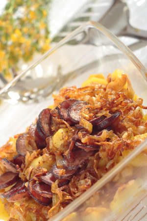 heatproof: Fried the onions pieces, the potatoes slices and the slices of sausage, roasted in glass heat-proof vessel. Slanting frame. In background blunt kitchen instruments and blossoms bouquet.
