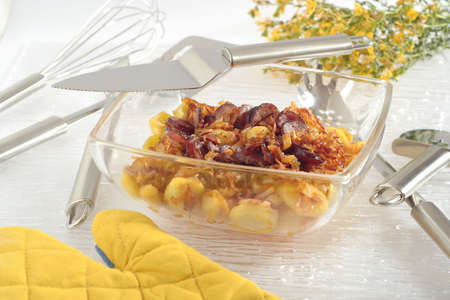 heatproof: Fried the onions pieces, the potatoes slices and the slices of sausage, roasted in glass heat-proof vessel. Oblique frame. Around vessel different kitchen instruments, glove and blossoms bouquet. Stock Photo