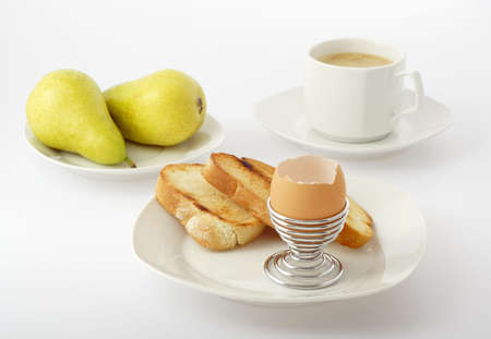 eggcup: Simple breakfast. Empty eggshell in wire eggcup, toast, two pears and the cup of coffee with foam. All arranged on small plates, on bright background dishes. Focus on eggshell in wire eggcup. Stock Photo
