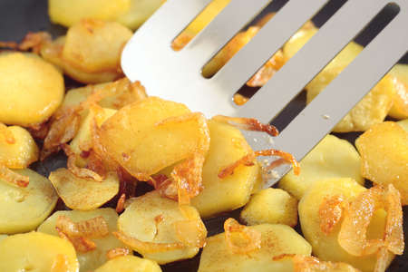 The close up view on fried potatoes slices with addition of chopped onion. In centre of frame the metal kitchen spatula.