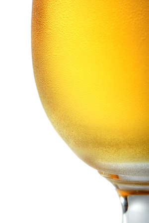 Cold beer in beer glass covered with small drops of condensed water.