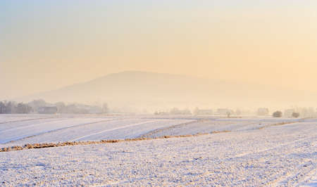 Small village in a hazy and snowy winter morning photo