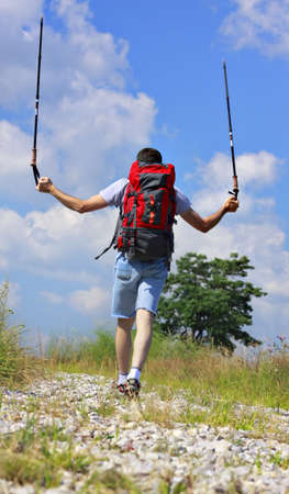 Hiker with backpack and trekking sticks up going on stony and grassy narrow path photo