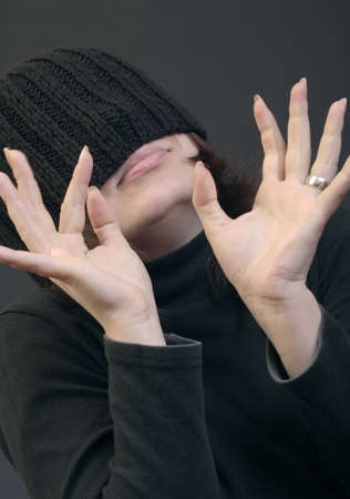 Young caucasian woman in woolen cap covered her eyes with hands gesture photo