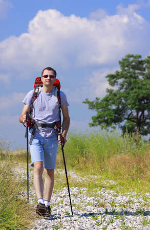 Walking hiker with backpack and trekking sticks on stony path photo