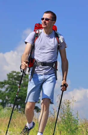 Hiker going on grassy meadow with unfocused tree and blue sky with clouds photo