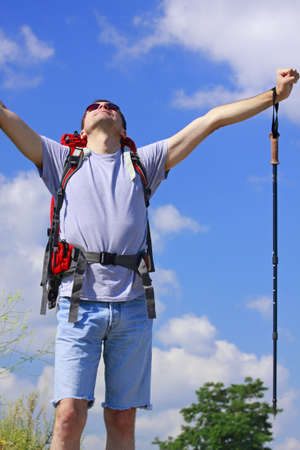Hiker with raised arms over blue sky with clouds Stock Photo - 7445406