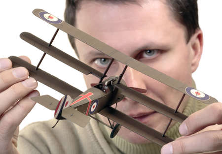 Man holding paper model of World War 1 fighter (Sopwith Triplane)