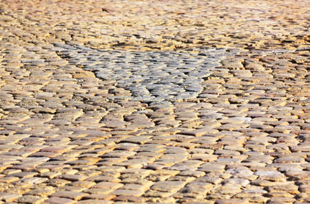 dichromatic: Granite dichromatic cobblestone pavement detail with triangle shape and limited DOF in warm morning light