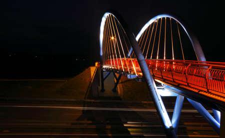Pedestrian bridge over road at night