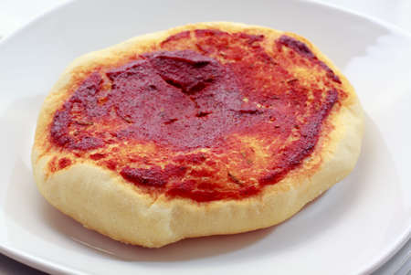 simplest: Small pizza (pizzette) with tomato sauce on white plate Stock Photo