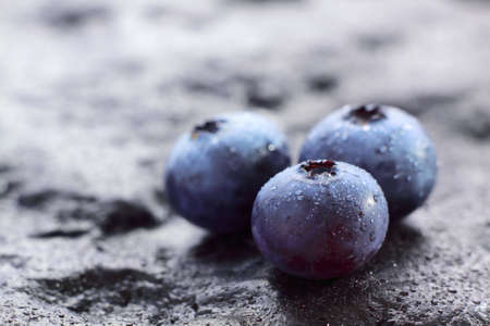 Blueberry (Northern Highbush Blueberry) fruits on dark painted stone with water drops