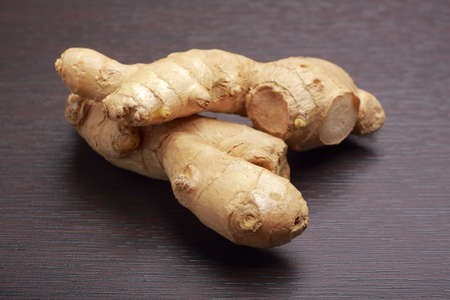 Ginger root (rhizome) lying on dark board