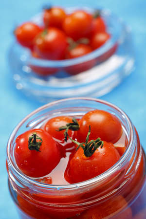 Cocktail tomatoes in opened jar with unfocused background photo