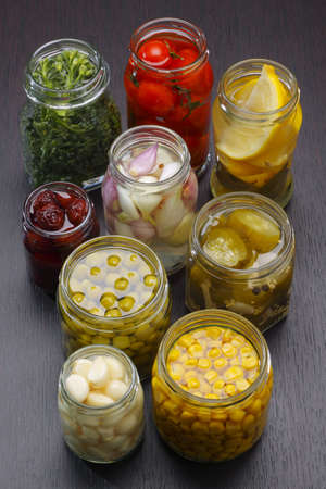 Opened jars with various preserved food on dark board