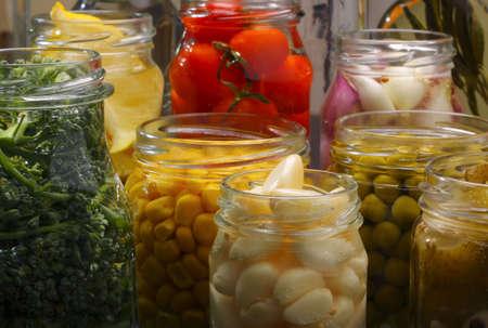 encurtidos: Abri� jarras en despensa con diversos alimentos conservados  Foto de archivo