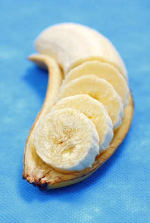 Partially sliced banana lying on its peel with shallow depth of field Stock Photo