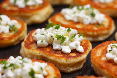 Close-up blinis (from white flour) with cottage cheese and chopped parsley