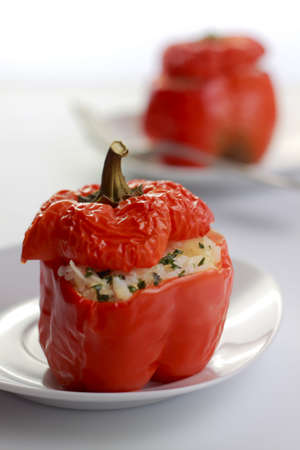 Roasted red peppers stuffed with rice on white plates. Shallow depth of field. Zdjęcie Seryjne