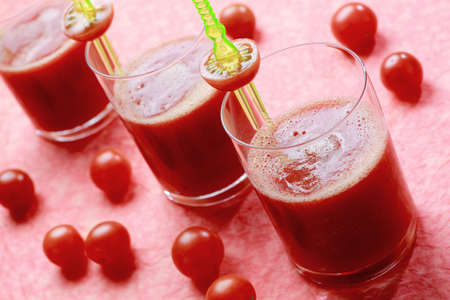 Three glasses with fresh tomato juice with cherry tomatoes. Focus on first glass. photo