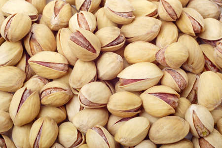 Background texture of pistachio nuts (Pistacia vera) in their shells. Close-up, full frame.