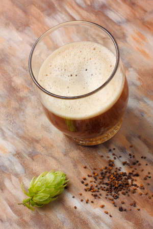 hop cone: Home made dark beer with its preparation ingredients (hop cone and home made malt)