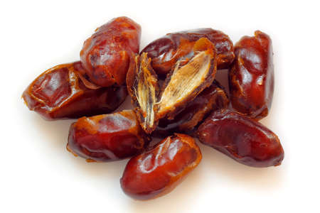pitted: A pile of pitted dried dates on white background