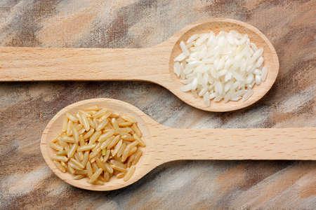 arroz blanco: Dos cucharas de madera con blanco y marrón granos de arroz sobre fondo pintado
