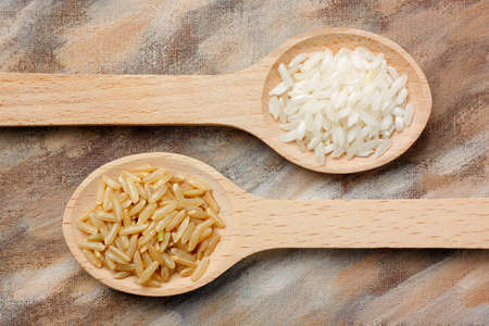 grains: Two wooden spoons with white and brown rice grains over painted background