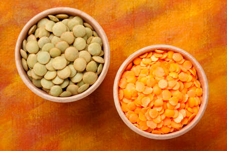 Top view of two wooden bowls with green and red lentils Lens culinaris