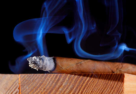 tip up: Cigar with abstract smoke. Wooden board, black background. Stock Photo