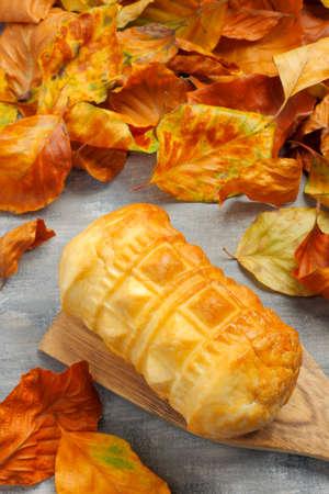 oscypek: Polish smoked cheese (oscypek) from Tatra Mountains region and dry autumn leaves Stock Photo