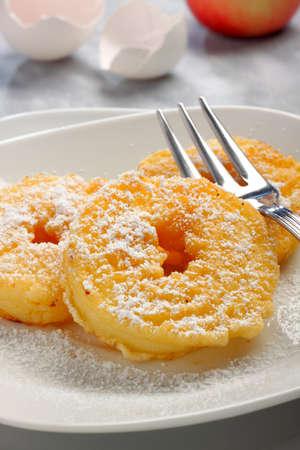 ringe: Gebratene Apfelringe mit Puderzucker auf Teller mit Gabel und unfocused Hintergrund Lizenzfreie Bilder