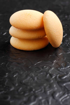 black textured background: Pile of sponge cakes on black painted textured background Stock Photo
