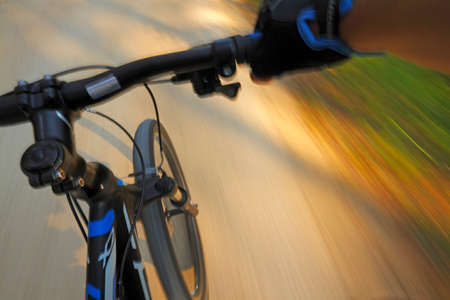 shady: Front part of a fast motion mountain bike on a shady road Stock Photo
