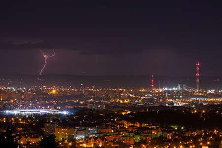 urbanized: Lightning storm over city skyline at night. Kielce, Poland, Holy Cross Mountains.