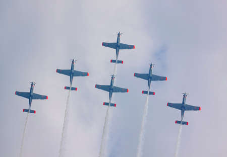 aerobatics: Upward view of a flying the Polish Air Force Orlik Aerobatics Team during International Air Show at the 90th Jubilee of The Polish Air Force Academy The School of Eaglets. Deblin, Poland, 20th June 2015.