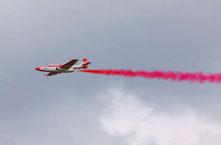 aerobatics: The Polish Air Force TS-11 Iskra MR of White-Red Sparks (Bialo-Czerwone Iskry) aerobatics team on fly with red smoke during International Air Show at the 90th Jubilee of The Polish Air Force Academy The School of Eaglets. Deblin, Poland, 20th June 2015. Editorial