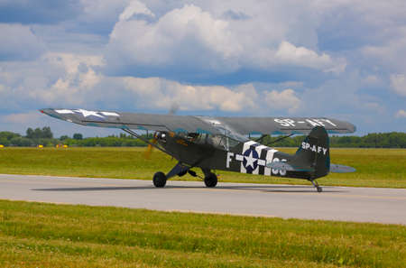 drab: The Piper J-3 Cub (L-4 Grasshopper; military markings) on runway during International Air Show at the 90th Jubilee of The Polish Air Force Academy The School of Eaglets. Deblin, Poland, 20th June 2015.