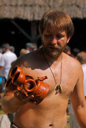 ceramicist: Portrait of craftsman with ceramic vessel at Archeological Festival Dymarki Swietokrzyskie. Nowa Slupia, Poland, 21-22 August 2010. Photo taken 22th August 2010. Editorial
