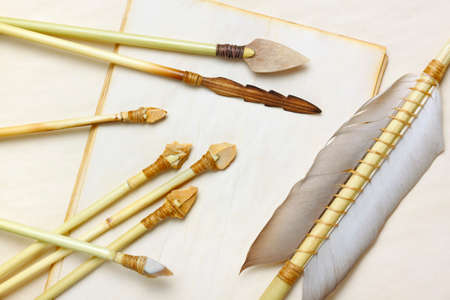 arrowheads: Primitive hunting and fishing arrows with flint stone, wood and bone arrowheads over aged paper sheets