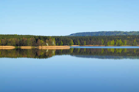 Lake with forest line mirrored into calm water surface. Cedzyna lake near Kielce. Poland, The Holy Cross Mountains.
