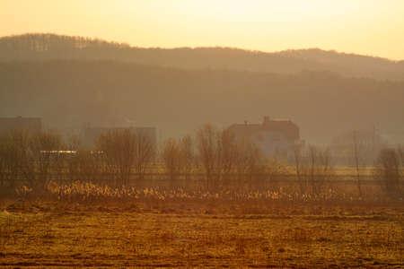Warm hazy sunrise over village. Poland, The Holy Cross Mountains. Reklamní fotografie - 104649210