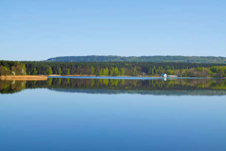 Lake with forest line mirrored into calm water surface. Cedzyna lake near Kielce. Poland, The Holy Cross Mountains. Reklamní fotografie - 120551172