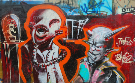 strangers: abstract ufo strangers graffity on the wall as a background Editorial