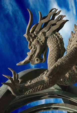 Bronze dragon on the blue sky background