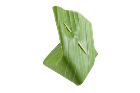 Banana leaf wrapped snacks Thai dessert, clip with bamboo stick isolated on white background photo