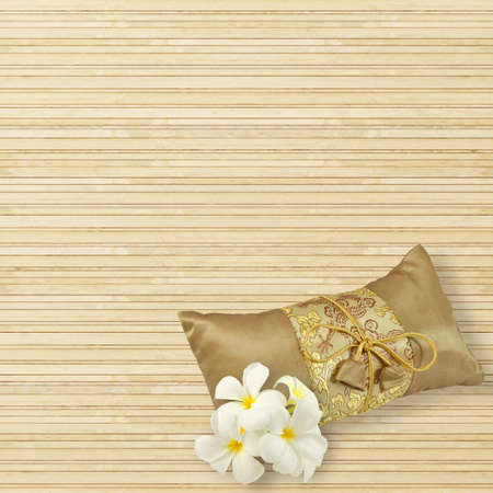 mat: Tradition gold silk pillow and plumeria flowers isolated on bamboo mat background Stock Photo