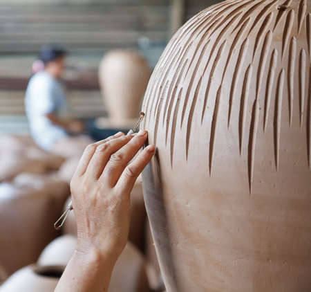 hands of Thai style pottery working on ceramic vase photo